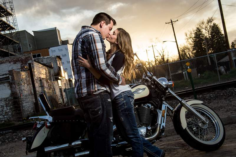 A couple by a motorcycle kiss at sunset during their urban engagement photo session in Fort Collins, Colorado.