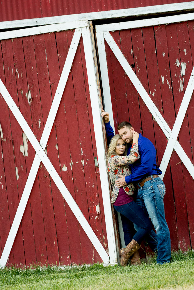 A couple holding eachother and leaning against a red barn door at their Fort Collins engagement photo session