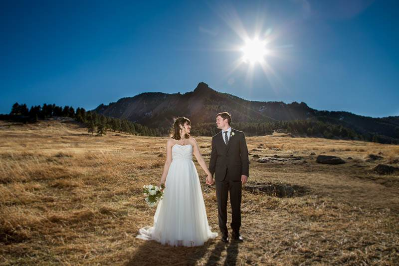 A bride and groom stand in front of the mountains at their modern Boulder, Colorado wedding.