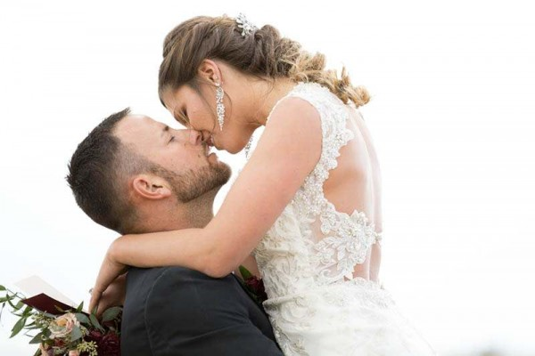 A stylish bride and groom share a kiss in a field near their modern Denver, Colorado wedding.