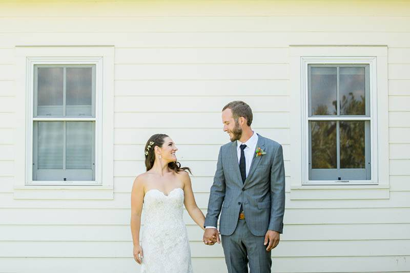 A couple stands in front of a yellow wall at their diy mountain wedding in Colorado.