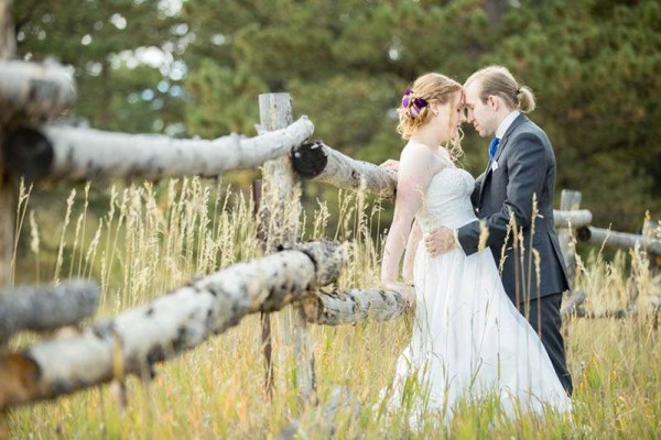 A bride and groom lean on a wooden fence in a mountain field at their Estes Park mountain wedding.