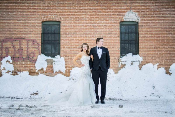 A modern colorado couple stand in front of a rustic brick wall at their old town fort collins winter wedding.
