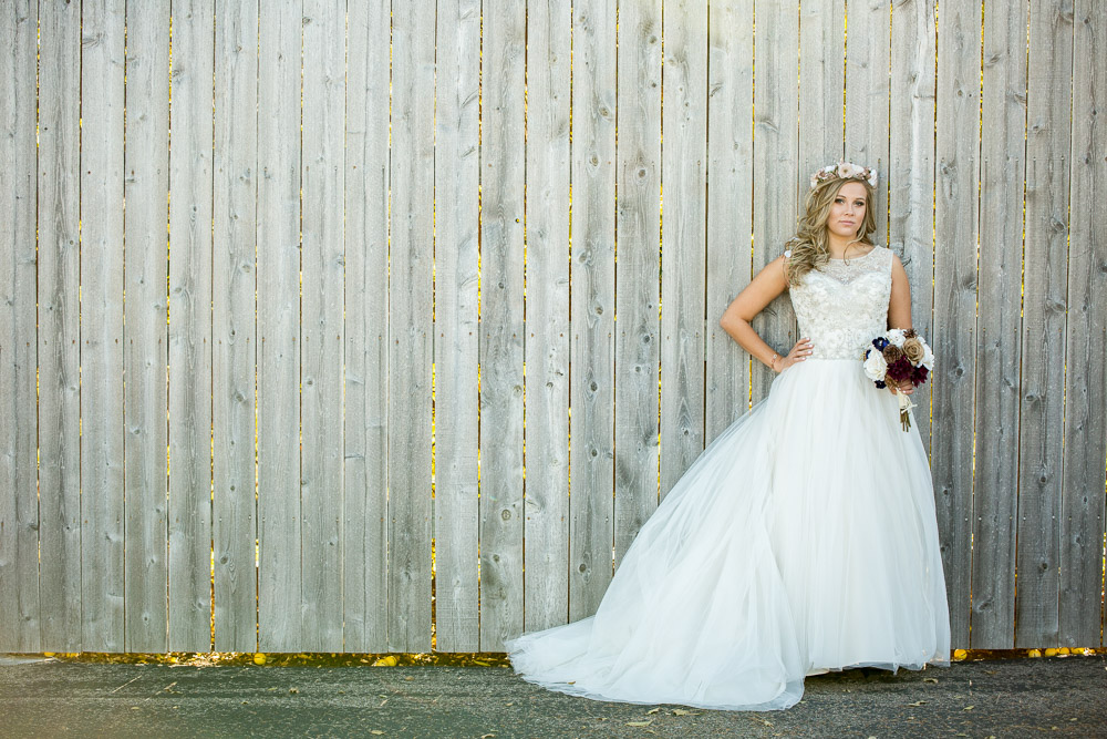 A bohemian Colorado bride stands in front of a wooden fence having her wedding portrait taken during her Greeley Country Club wedding.