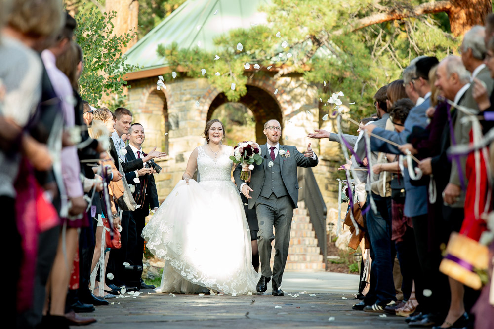 A bride and groom exit thier wedding ceremony at Della Terra Mountain Chateau while guests throw flower petals.
