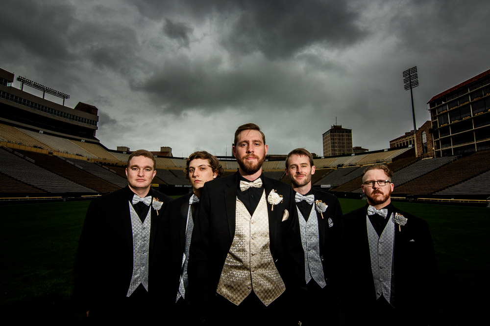 A groom and his groomsmen stand on the Football field at his wedding at Folsom field in Boulder, Colorado.