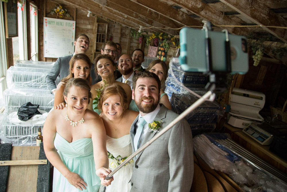 A bridal party taking a selfie during a rainy wedding at Happy Heart Farm in Fort Collins.
