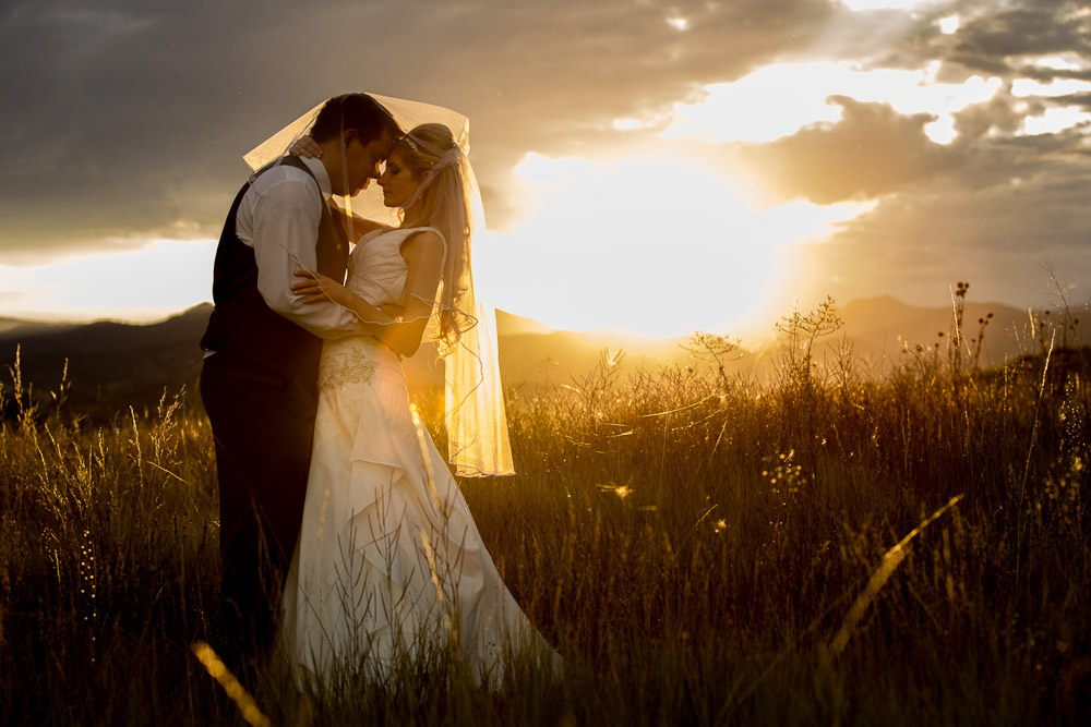 A bride and groom under a mountain sunset in a field after their Fort Collins wedding.