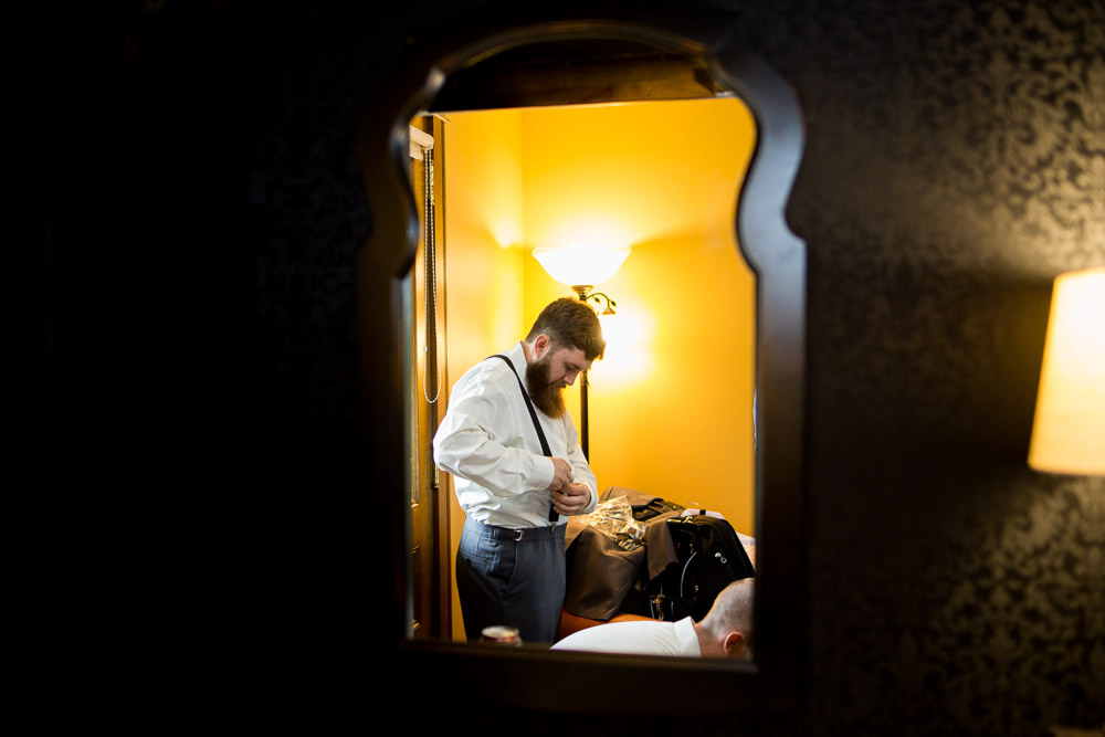 A reflection of a groom in the mirror as he prepares for his Tapestry House wedding in Fort Collins.