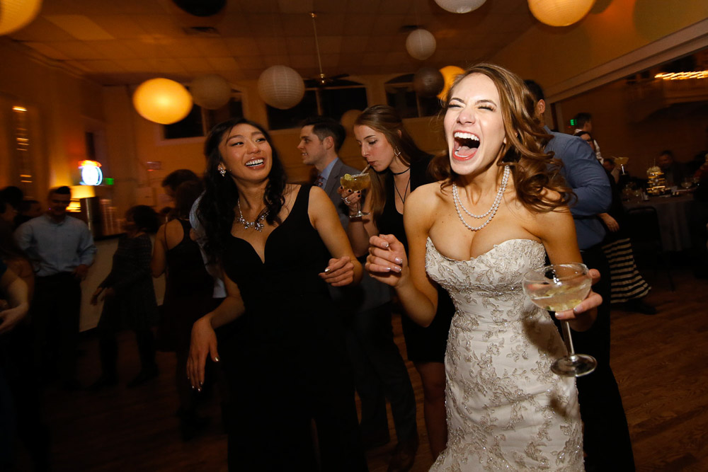 A modern Colorado bride laughing on the dance floor at her Old Town Fort Collins winter wedding.